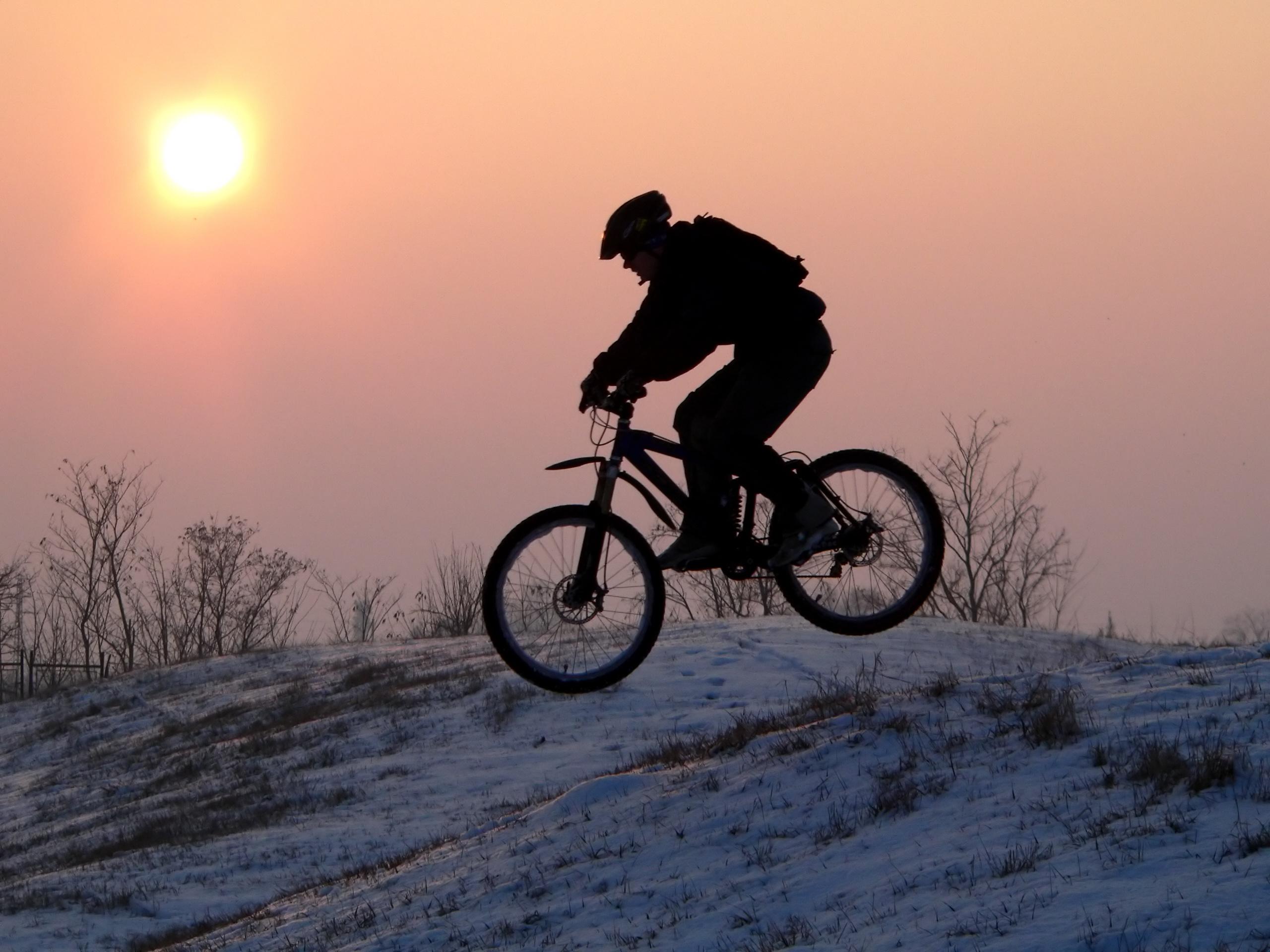 Winter Biking - Biker on snow covered hill